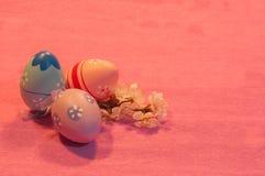 与开花的杏子枝杈的三个复活节彩蛋在桃红色 库存图片