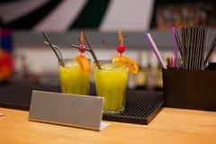与异乎寻常的鸡尾酒的两块玻璃在酒吧柜台 免版税库存图片