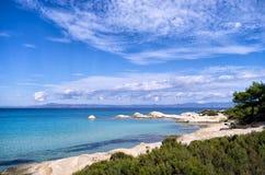 与异乎寻常的水和小的含沙海湾的岩石海岸,在哈尔基季基州,希腊 免版税库存图片