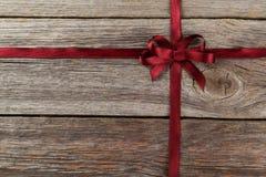与弓的伯根地丝带在木背景 免版税库存图片