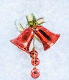 与弓的圣诞节铃声在发光的背景雪花 免版税库存图片