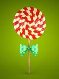 与弓的棒棒糖在绿色背景 免版税库存图片