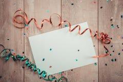 与弓的白纸板料在木背景 免版税库存图片