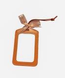 与弓的空白的橙色浅褐色的皮革名牌在白色背景 免版税库存图片