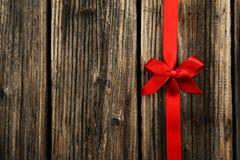与弓的红色丝带在棕色木背景 免版税库存图片