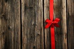 与弓的红色丝带在棕色木背景 图库摄影