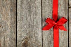 与弓的红色丝带在灰色木背景 免版税库存图片