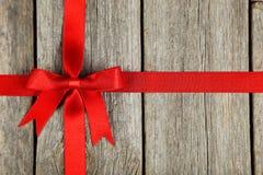 与弓的红色丝带在灰色木背景 免版税图库摄影