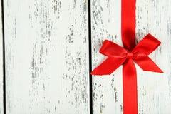 与弓的红色丝带在白色木背景 免版税库存图片