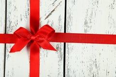 与弓的红色丝带在白色木背景 库存照片
