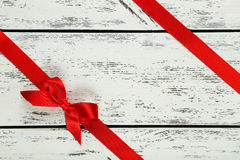 与弓的红色丝带在白色木背景 免版税库存照片