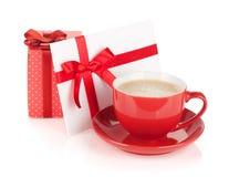 与弓的红色咖啡杯、礼物盒和情书 免版税库存照片