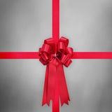 与弓的红色缎丝带在灰色背景 免版税库存照片