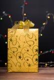 与弓的金黄礼物盒 免版税库存图片