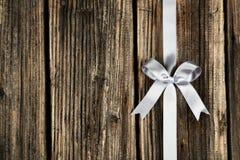 与弓的银色丝带在棕色木背景 免版税库存图片