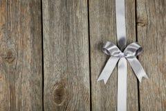 与弓的银色丝带在灰色木背景 免版税库存照片