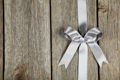 与弓的银色丝带在灰色木背景 图库摄影