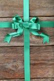 与弓的绿色丝带在木背景 库存照片