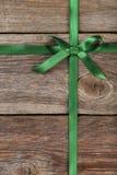 与弓的绿色丝带在木背景 免版税库存照片