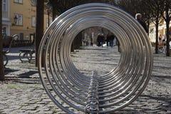 与弯曲的圈子的空的银色金属自行车立场 库存图片