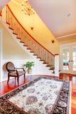 与弯曲的楼梯和豪华地毯的入口与椅子。 免版税库存照片