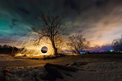 与弹道的抽象图片烧发火花靠近树在夜风景背景  库存图片