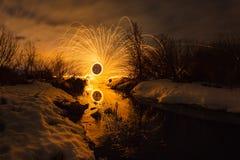 与弹道的抽象图片烧在表面小河发火花在春天风景背景  图库摄影