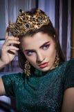 与强有力的严密的神色的美好的时尚女孩模型在金黄冠 免版税库存图片