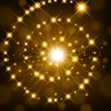 与形成螺旋背景的闪闪发光的金黄亮光 免版税库存照片