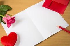 与形状心脏枕头的红色信封在文本爱和上升了 免版税库存图片