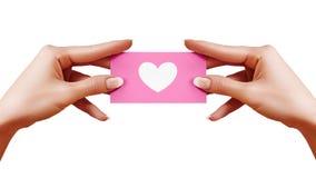 与形状心脏的情人节明信片在白色背景的女性手上 桃红色礼品券 爱和幸福标志 图库摄影