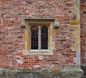 与彩色玻璃的老华丽具体窗口在一个被风化的砖墙在一所老庄园住宅里 免版税库存照片