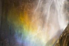 与彩虹关闭的背景有薄雾的瀑布 免版税库存照片