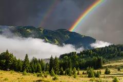 与彩虹和薄雾的美好的山风景 免版税图库摄影