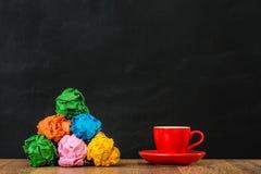 与彩虹纸球的红色咖啡杯小组 免版税库存照片