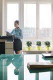 与影印件的少妇复制的文件在办公室 免版税图库摄影