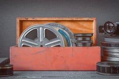 与影片的卷轴在一个木箱、透镜和一个老电影摄影机 免版税库存照片