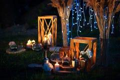 与很多光的夜婚礼,蜡烛,灯笼 美丽的浪漫光亮的装饰在微明下 免版税图库摄影