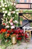 与很多鲜花和蜡烛的婚礼曲拱在地板上 花装饰 免版税库存图片