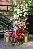 与很多鲜花和蜡烛的婚礼曲拱在地板上 花装饰 免版税库存照片