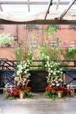 与很多鲜花和蜡烛的婚礼曲拱在地板上 花装饰 库存图片