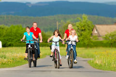 与循环在与自行车的夏天的孩子的家庭 免版税库存图片