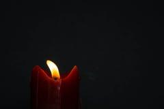 与微光光火焰的老红色蜡烛在好的灰色背景,与空白的上部空间 库存照片
