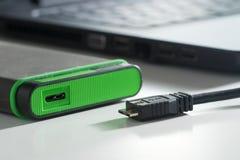 与微型usb缆绳的绿色外置硬盘 免版税库存照片