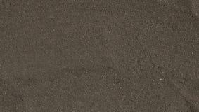 与微小的石头的黑暗的沙子背景 免版税图库摄影