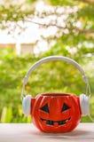与微笑和耳机的音乐爱好者南瓜 万圣夜天 免版税库存图片
