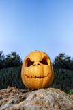 与微笑的万圣夜可怕南瓜在岩石 库存照片