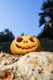 与微笑的万圣夜可怕南瓜在岩石 免版税库存照片