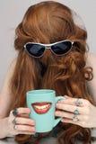 与微笑的咖啡杯的美丽的红头发人 库存照片