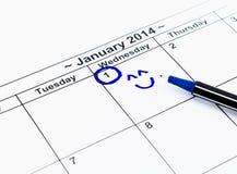 与微笑的蓝色圈子。在日历的标记在2014年1月1日 图库摄影
